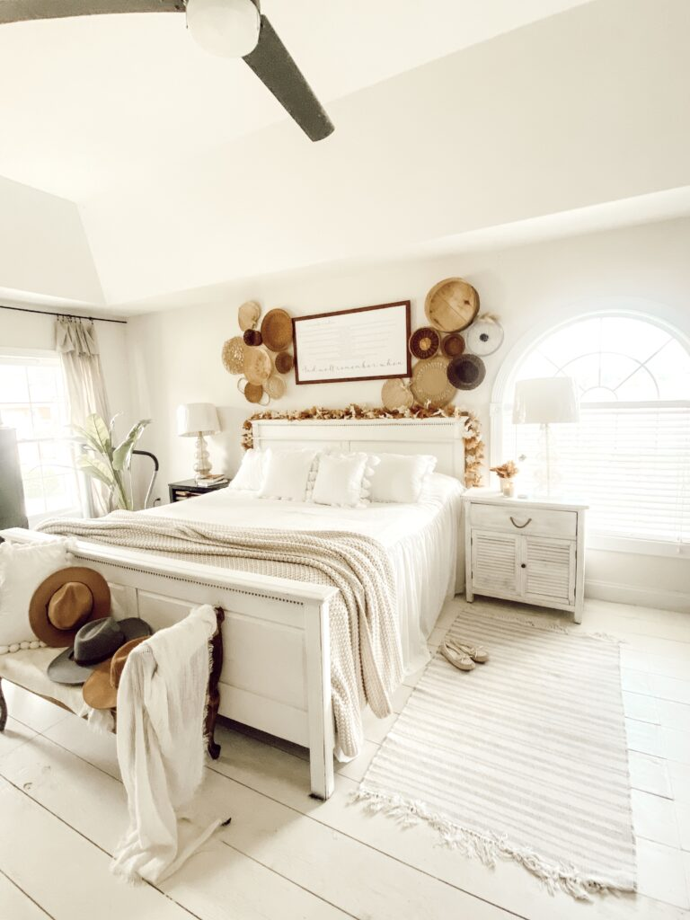 white farmhouse master bedroom with framed song lyrics and a basket wall